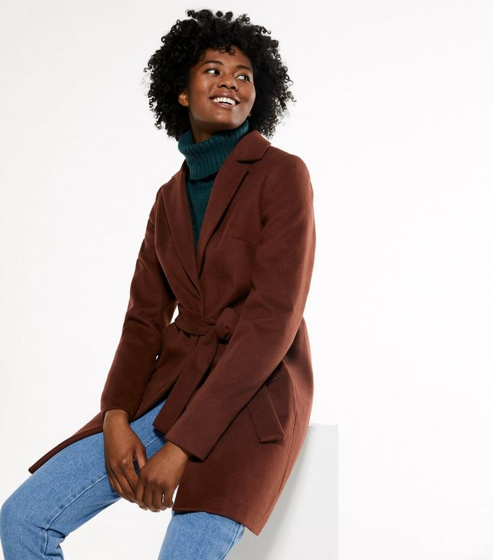 Vegan coat in a wine red colour with belt worn by a woman who is also wearing bluejeans