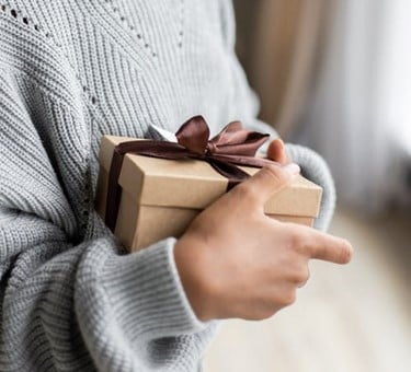 person with grey jumper holding a small cardboard box wrapped in ribbon
