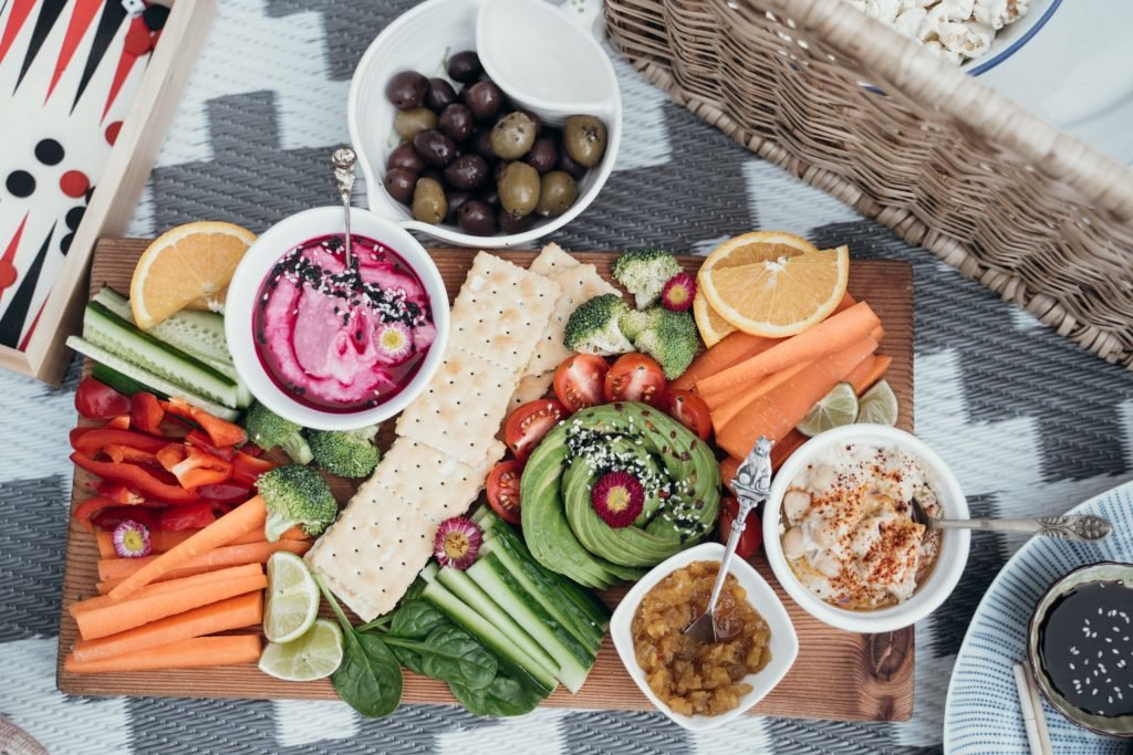 Picnic Spread with Vegetables, Crackers, Dips and Fruit on Grey and White Blanket.